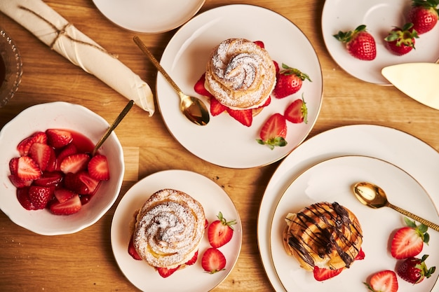 Overhead shot of delicious cream puff with strawberries and chocolate on a wooden table