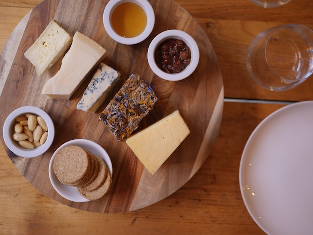Overhead shot of different cheeses on a round wooden tray near different sauce and biscuits