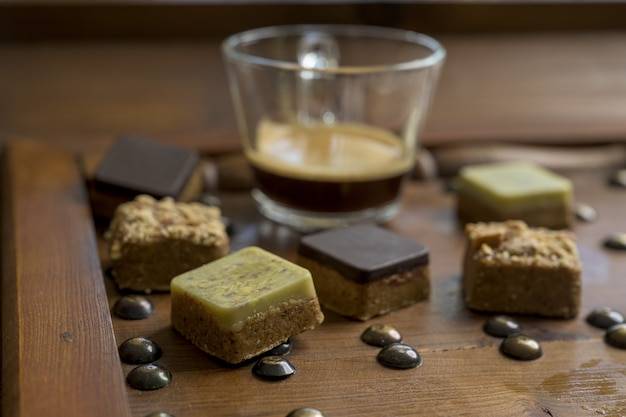 Overhead shot of different types of square-shaped sweets with tea on a wooden tray