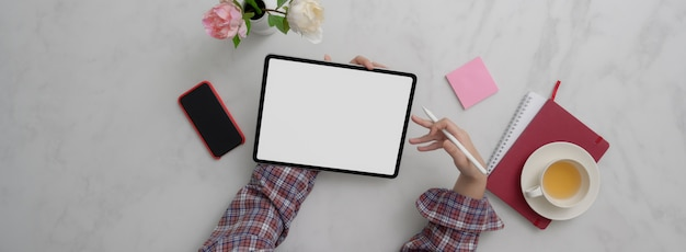 Overhead shot of female entrepreneur working with mock-up tablet, smartphone and other supplies