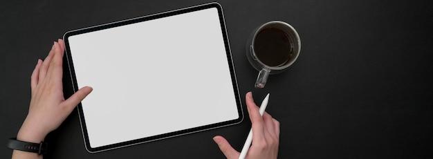 Overhead shot of female freelancer working on mock-up tablet at dark modern workspace