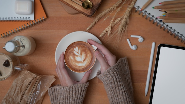 Overhead shot of female hands holding a cup of latte coffee on wooden worktable with mock up tablet and supplies