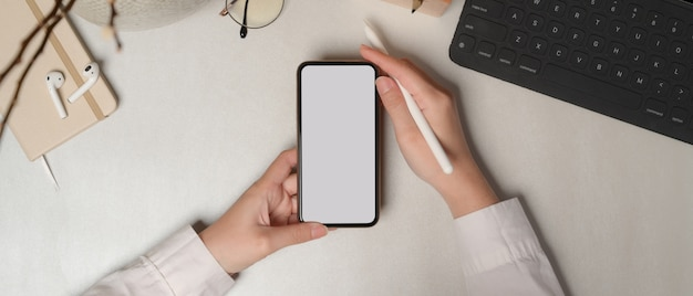 Overhead shot of female hands holding smartphone with clipping path on white table with office supplies