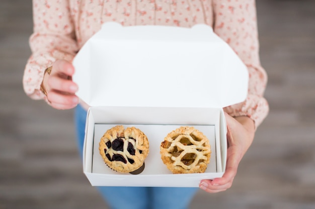 Overhead shot of a female holding a white box containing two small pastries