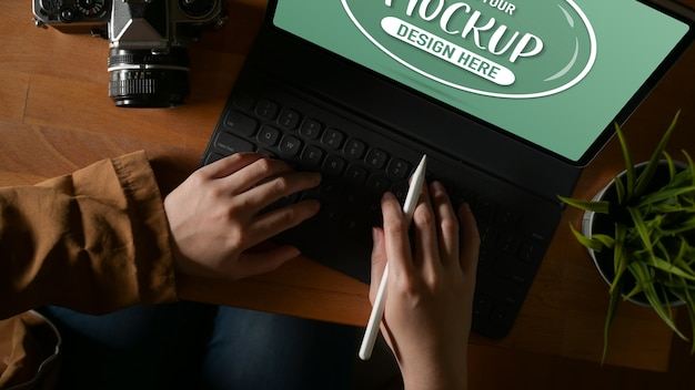 Overhead shot of female typing on mock up tablet keyboard while holding stylus pen on wooden table