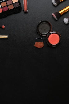 Overhead shot of feminine desk with with lipsticks, eye palette, face powder, brushes and copy space on dark background.