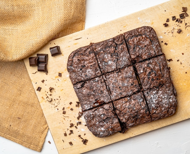 Overhead shot of freshly baked brownies on a wooden board
