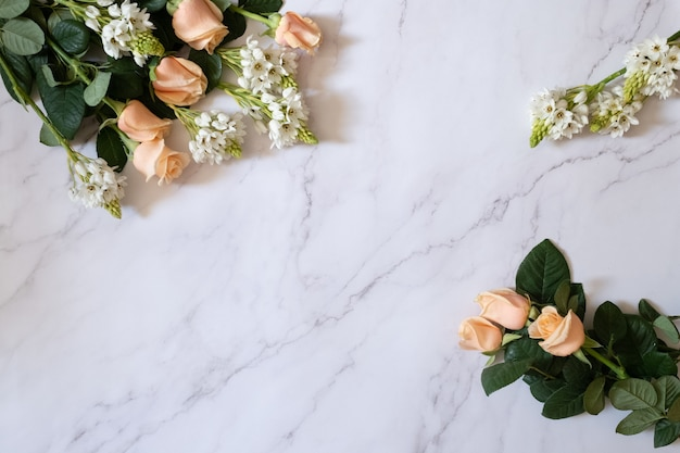 Overhead shot of garden roses with green leaves and white small flowers on a white marble surface