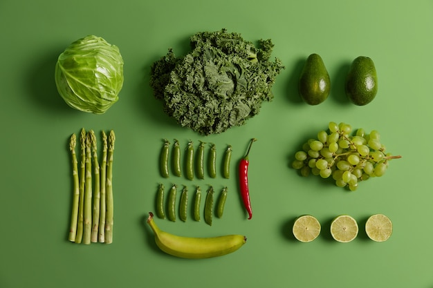 Overhead shot of green fruit and vegetables for your healthy nutrition. cabbage, asparagus, avocado, peas, bananas, lime, red chili pepper and grapes. collection of organic ingredients to eat