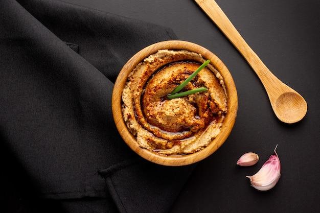 Scatto dall'alto di hummus in una ciotola di legno con un cucchiaio di legno e pezzi di aglio sulla tavola nera