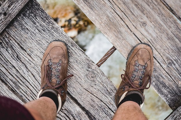 Overhead shot of a male feet standing on a wooden bridge wearing hiking shoes