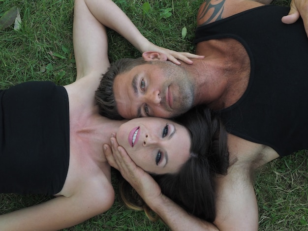 Overhead shot of a male and a female lying on the grass cheek to cheek