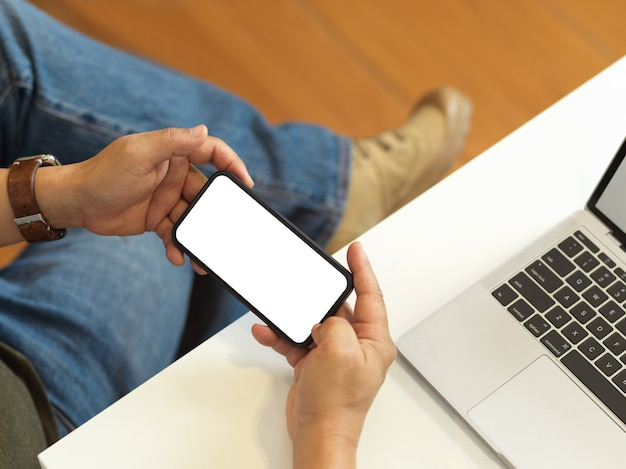 Overhead shot of male freelancer holding smartphone with horizontal screen on workspace