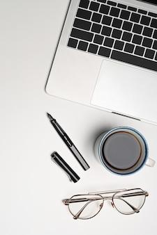 Накладные выстрелы макет ноутбука, чашки кофе и очков на белом фоне.
