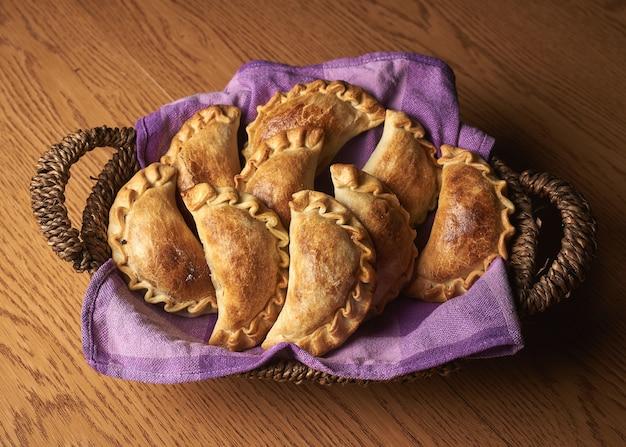 보라색 냅킨에 갓 구운 파이가있는 바구니의 오버 헤드 샷