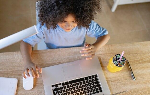 컴퓨터 노트북과 오렌지 주스를 가지고 집에서 숙제를 하는 아이의 머리 위 사진