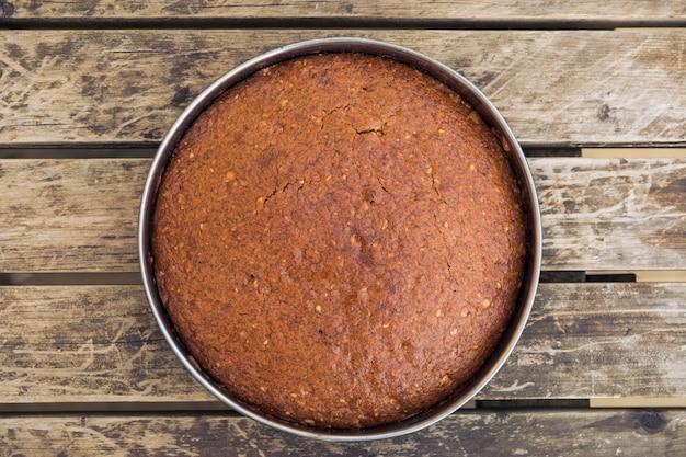 나무 표면에 둥근 금형에 맛있게 구운 케이크의 오버 헤드 샷
