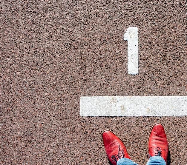 番号「1」の行の前に立っている赤い靴を履いた男のオーバーヘッドショット