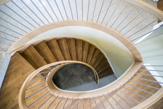 Вид сверху деревянной винтовой лестницы в современном доме