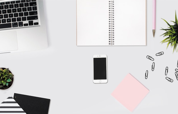노트북, 분홍색 스티커 메모 및 종이 클립 흰색 책상에 스마트 폰의 오버 헤드 샷
