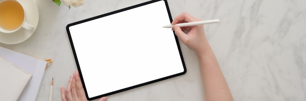 Накладные выстрел женщины, работающие на пустой экран планшета на мраморном столе