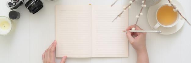 Накладные выстрел женщины, пишущей на пустой дневник тетради на доске