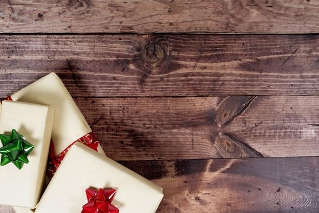 休日のテキストを書くのに最適な下側にプレゼントがある木製の表面のオーバーヘッドショット