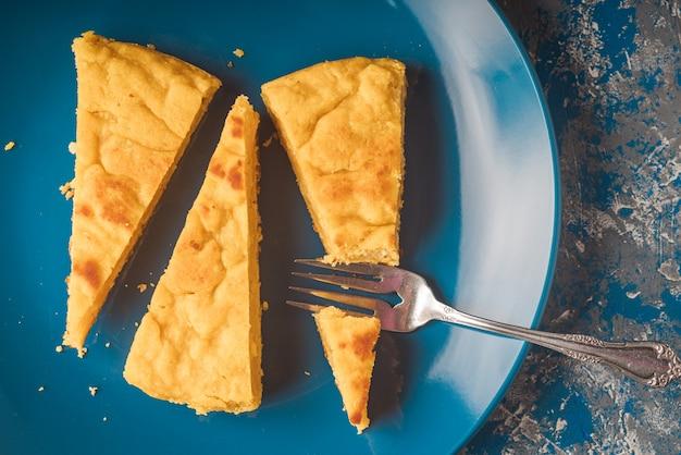Верхний снимок желтого торта на синей тарелке