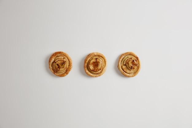 白い背景で隔離、あなたの消費の準備ができて食欲をそそる甘い渦巻きキャラメルバニラパンのオーバーヘッドショット。パン屋さんの美味しいスイーツ。ベーカリー製品自家製ケーキ