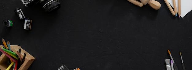 Верхний снимок рабочей области художника с бумагой эскиза, инструментами рисования, камерой и пространством копии