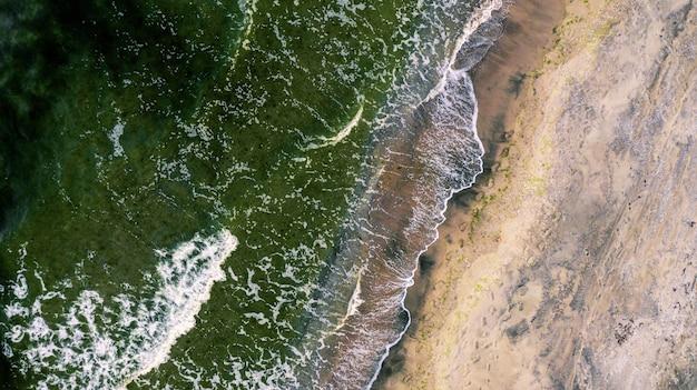 해안을 향해 오는 해변 파도의 오버 헤드 샷