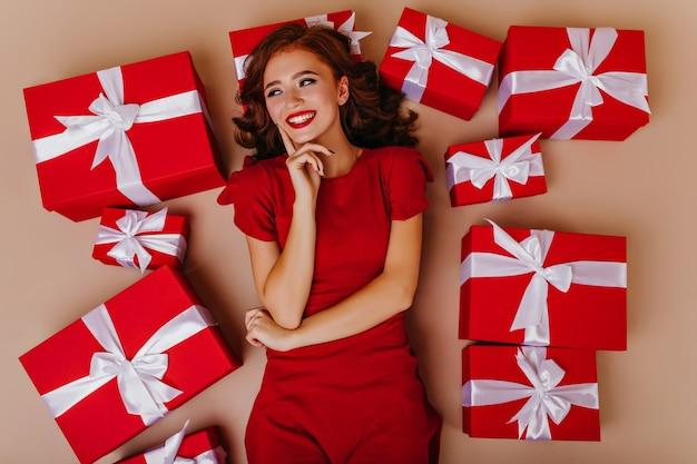 Снимок веселой великолепной девушки, лежащей на полу в день рождения. портрет дамы имбиря в окружении рождественских подарков.
