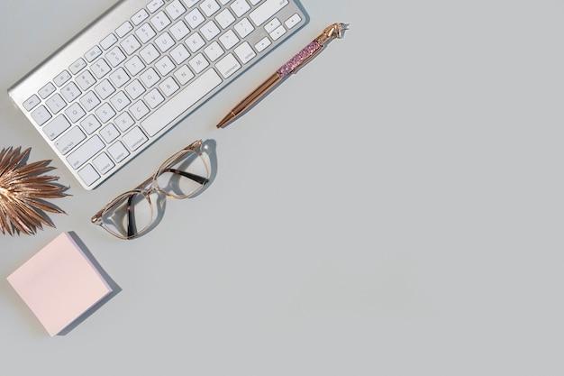 복사 공간이 있는 회색 배경에 키보드, 안경, 펜이 있는 비즈니스 데스크탑의 오버헤드 샷