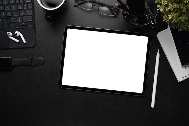 디지털 태블릿, 무선 이어폰, 스마트 시계, 노트북이 있는 어두운 사무실 책상의 오버헤드 샷.