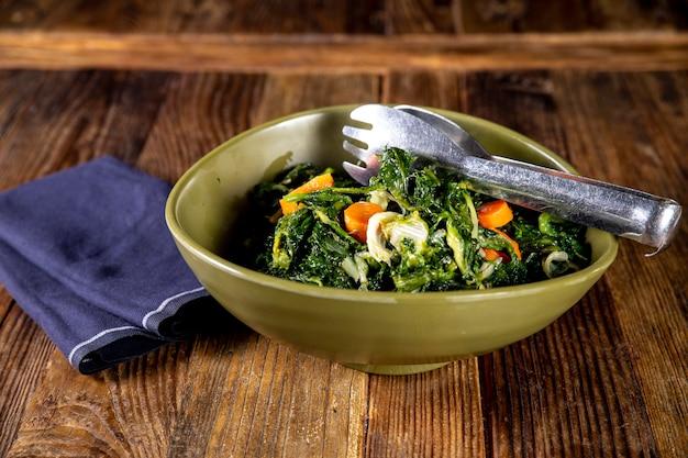 ステンレス鋼のトングでおいしい新鮮なサラダ野菜のオーバーヘッドショット