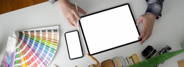 빈 화면 태블릿 및 스마트 폰 작업 여성 디자이너의 오버 헤드 샷