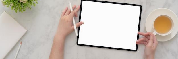 Накладные выстрел из фрилансера женского пола, работающего над макетом планшета на мраморном столе