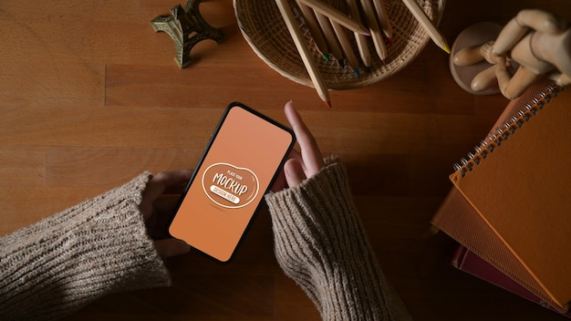 Верхний снимок женских рук, держащих макет смартфона на учебном столе