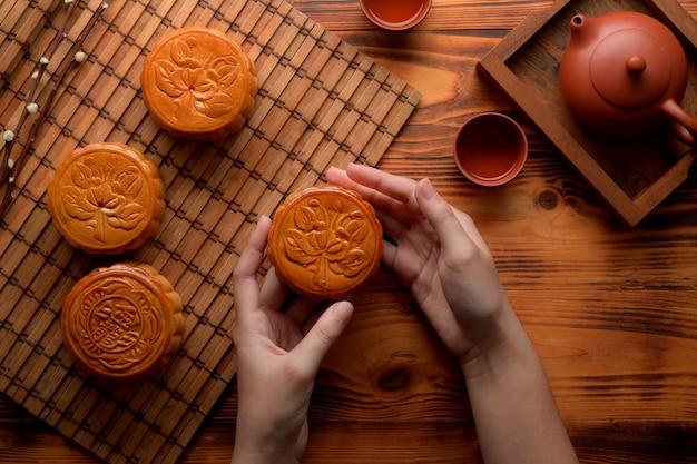 月祭のテーブルセッティングの上の月餅を保持している女性の手のオーバーヘッドショット。月餅の漢字は英語で「五穀とローストポーク」を表す
