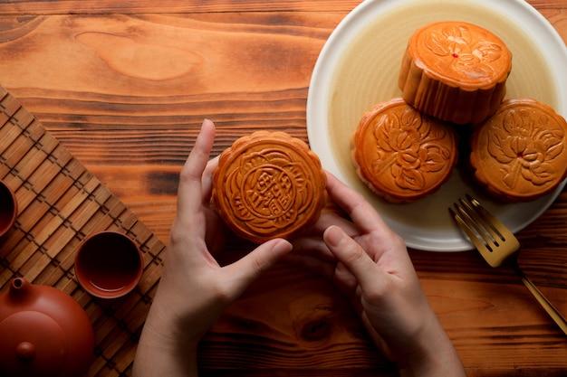 素朴なテーブルに伝統的な月餅を保持している女性の手のオーバーヘッドショット。月餅の漢字は英語で「五穀とローストポーク」を表す