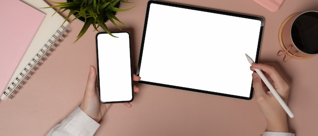 Верхний снимок женщины, работающей со смартфоном и планшетом с обтравочным контуром на розовом офисном столе
