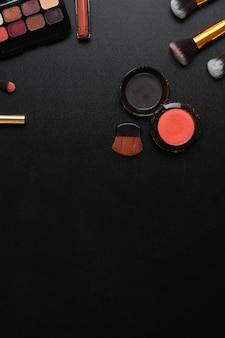 口紅、アイパレット、フェイスパウダー、ブラシ、暗い背景のコピースペースを備えたフェミニンなデスクのオーバーヘッドショット。