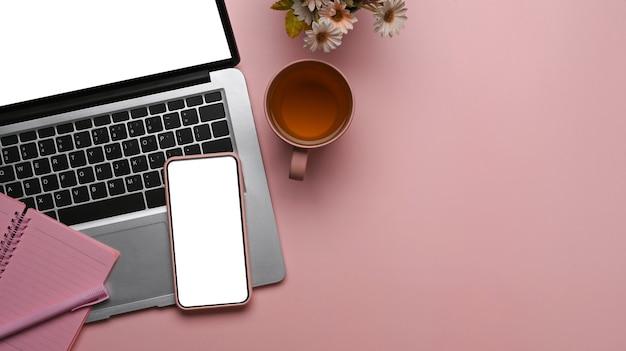 분홍색 배경에 스마트 폰, 노트북, 노트북 및 복사 공간이 있는 여성 작업 공간의 오버헤드 샷.