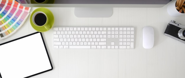 空白の画面のタブレット、コンピューターデバイス、デザイナー用品を備えたグラフィックデザイナーワークスペースのオーバーヘッドショット