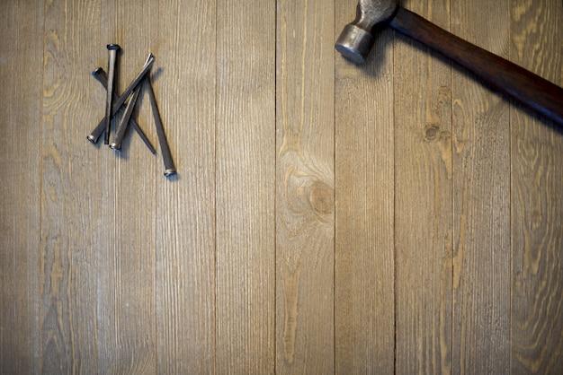 ハンマーと木の表面に釘のオーバーヘッドショット