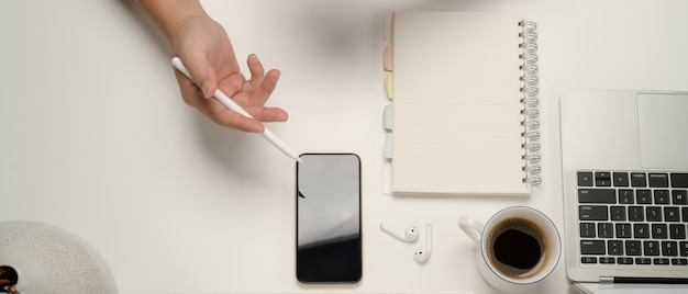 Верхний снимок руки, держащей стилус и указывающей на экран смартфона