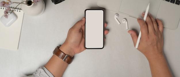 Верхний снимок мужских рук с помощью смартфона с обтравочным контуром на офисном столе с аксессуарами и украшениями