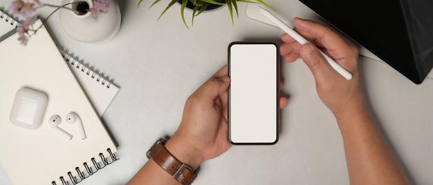 Верхний снимок мужских рук, использующих смартфон с обтравочным контуром на офисном столе с принадлежностями и аксессуарами