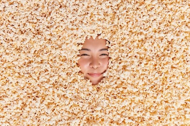 짭짤한 팝콘에 익사한 신비한 젊은 아시아 여성의 머리 위 사진은 즐거운 표정으로 맛있는 간식을 먹고 영화에서 자유 시간을 보낸다