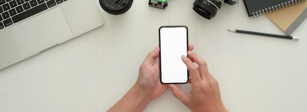 白い作業台でモックアップのスマートフォンを使用して写真家の俯瞰写真
